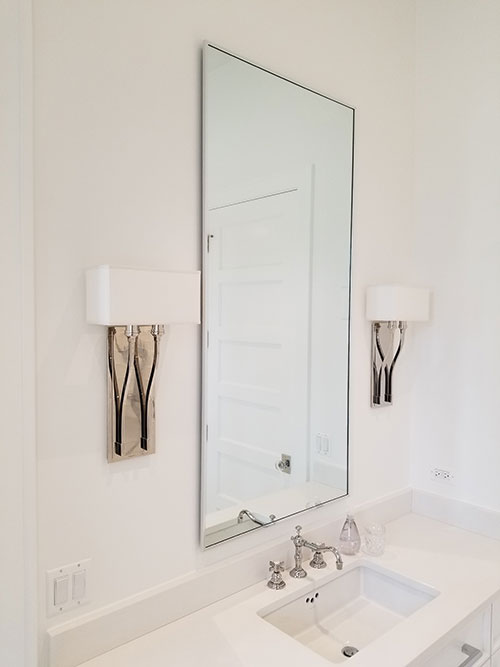 Modern and stylized mirror with classy lamps.